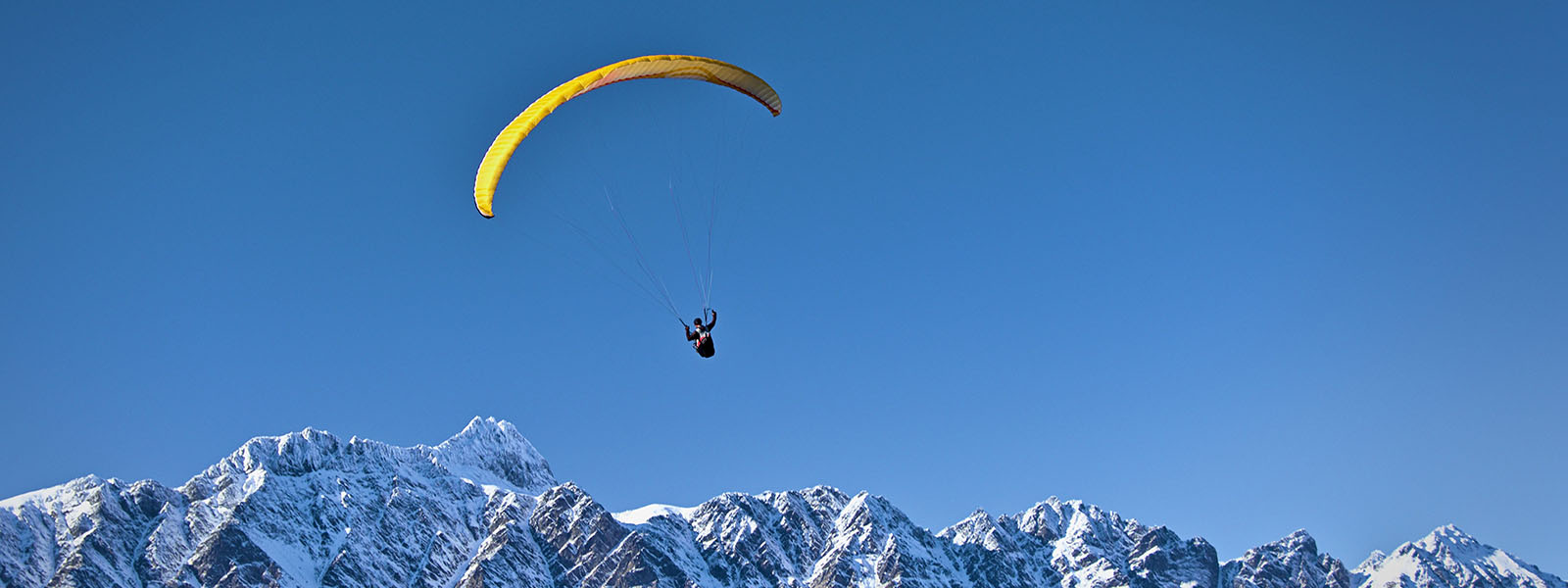Paraglider above Remarkables range, Queenstown, Otago, New Zealand